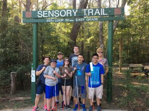 several students stand in front of a sign that says sensory trail. it's in australia. the students smile and they are holding white canes.