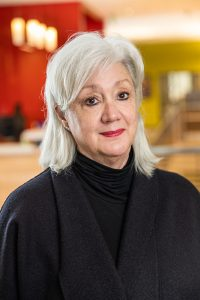 Portrait of Meghan Holbrook with shoulder length silver hair, wearing black