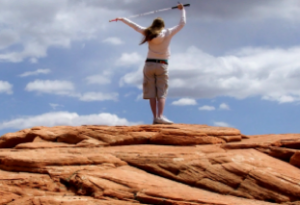 Girl stands on top of red rocks holding a white cane over her head