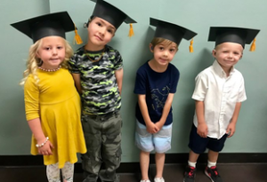 Four young students wearing graduation caps